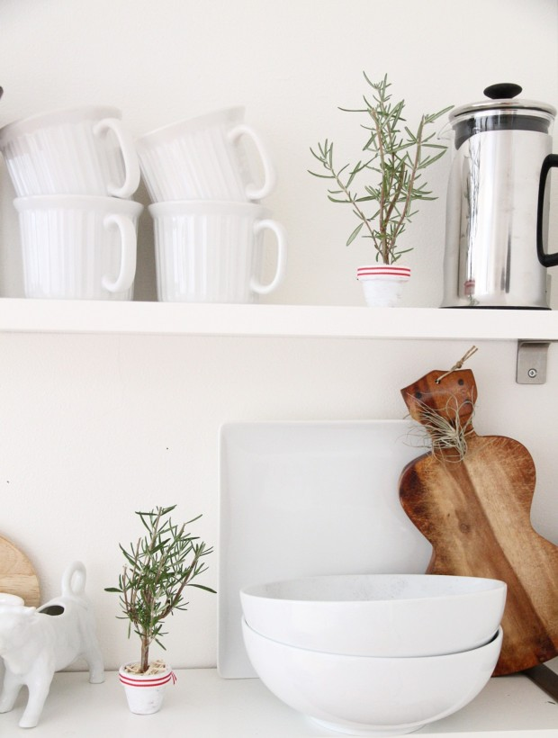 White kitchen with wooden bread board, and white dishes with the little tree on the counter.