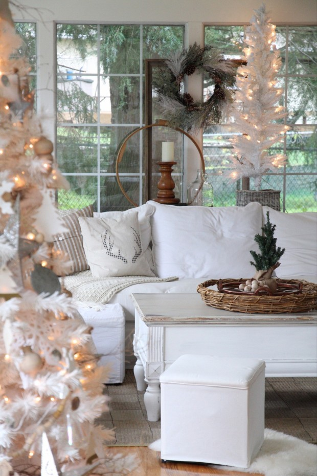 White couch with antler pillow on it, and white Christmas trees all lit up.