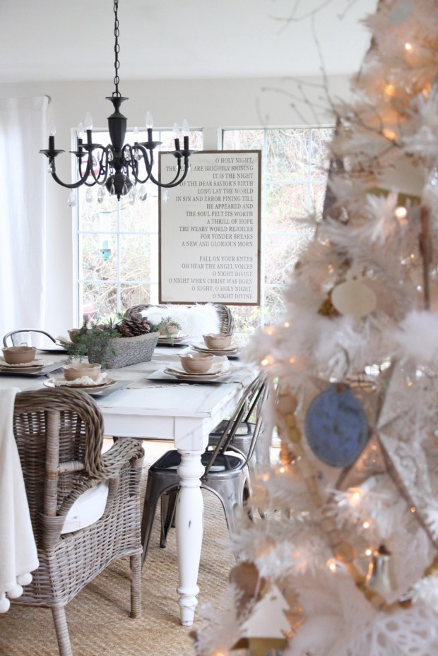 White kitchen table with a black chandelier above it and a lit tree beside the table.