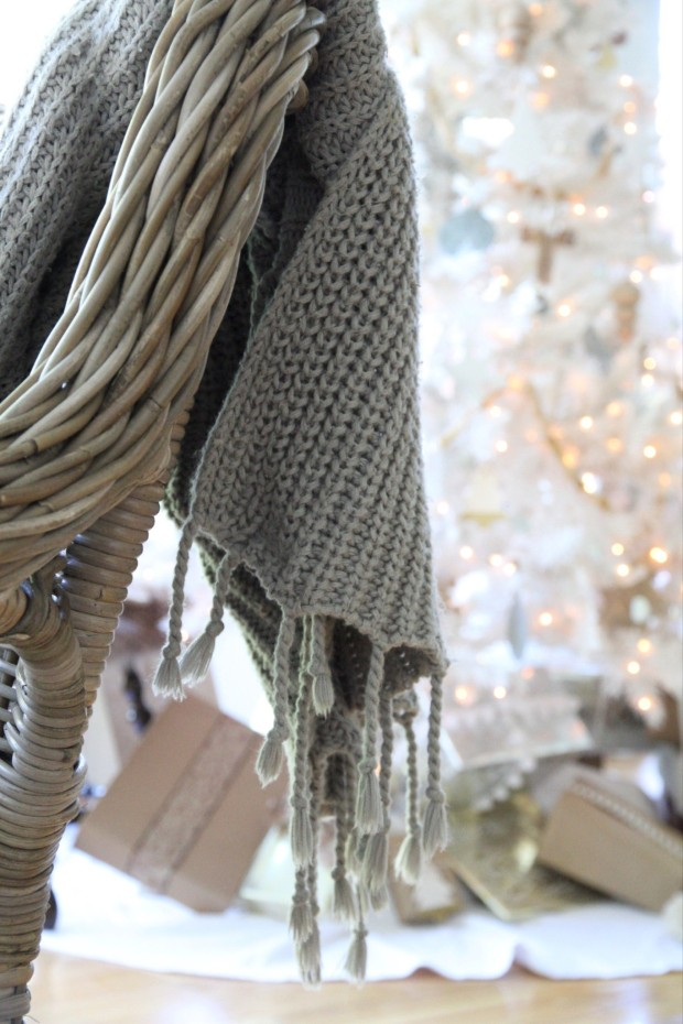 A knitted gray throw hanging on the back of the kitchen chair.