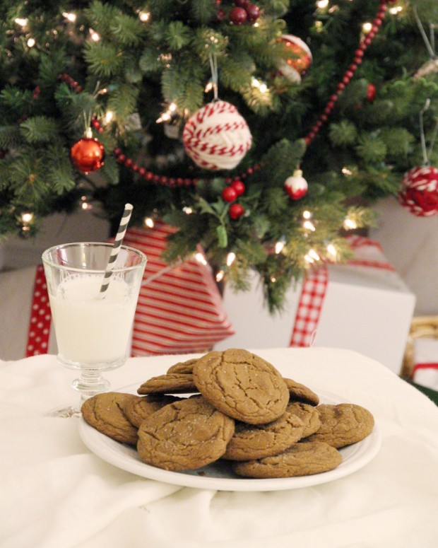 A christmas tree decorated with red and white ornaments and a plate of cookies beside it.