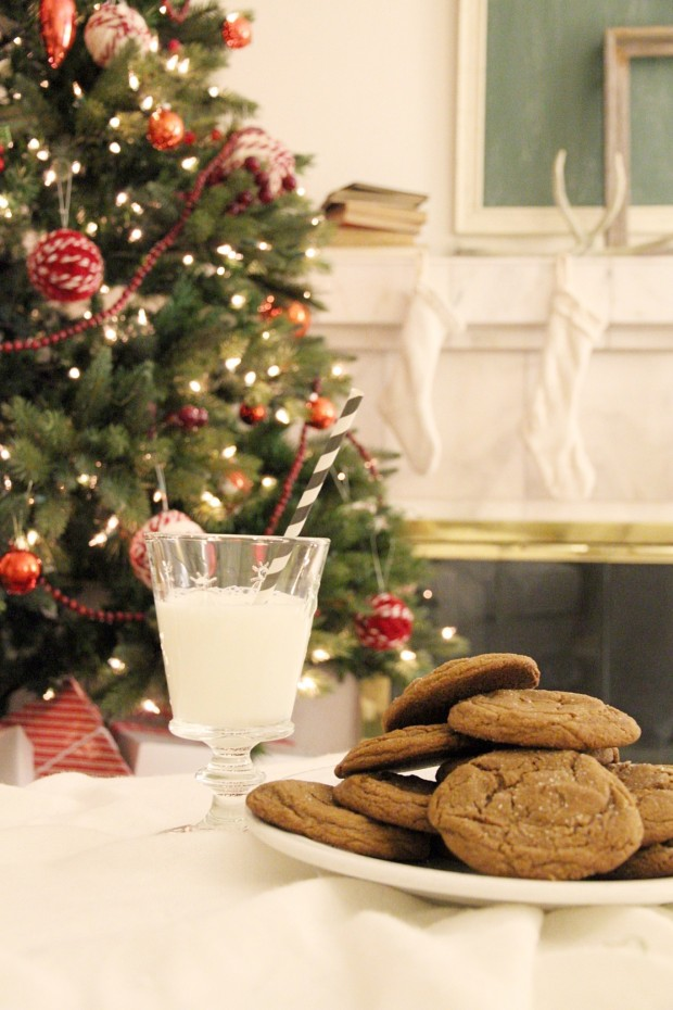 Decorated Christmas tree, a glass of milk, molasses cookies on a plate.