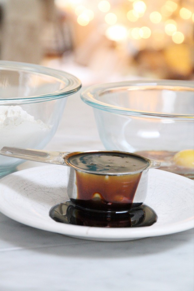 A metal measuring cup with molasses spilling out onto a white plate.