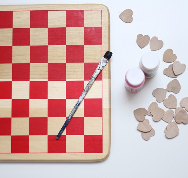 A checker board, a paint brush, and unpainted hearts on the table.