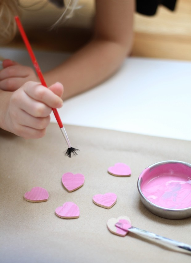 Pink paint in a small container and children painting the heart pieces.