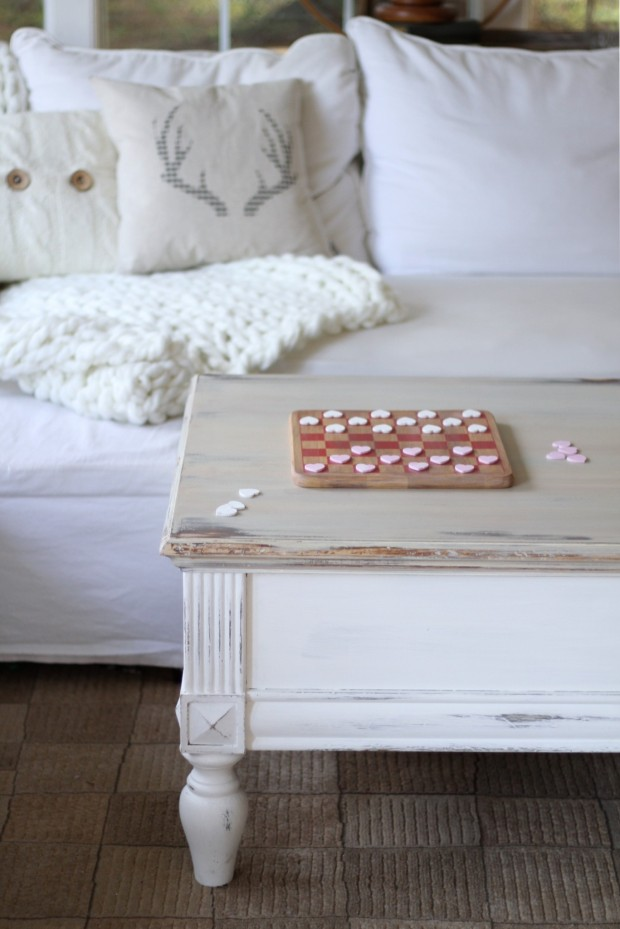 The game of Valentine checkers on a white coffee table in front of a white couch.