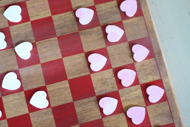 The pink heart pieces on the red and wood checker board.