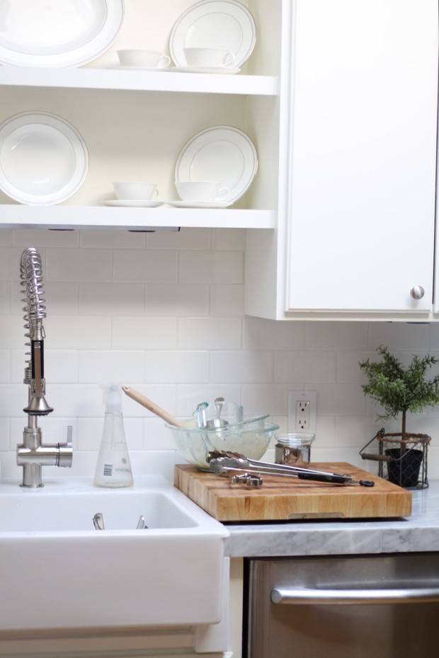 A white kitchen with a cutting board on the counter and an industrial style faucet.