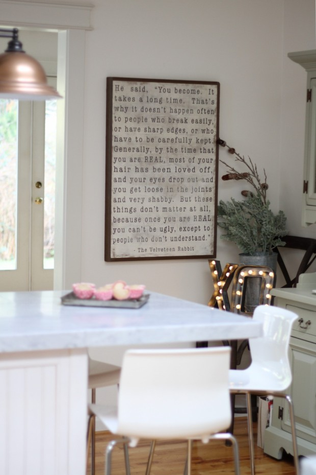 A white kitchen with muffins on the counter and a large graphic picture hanging up.