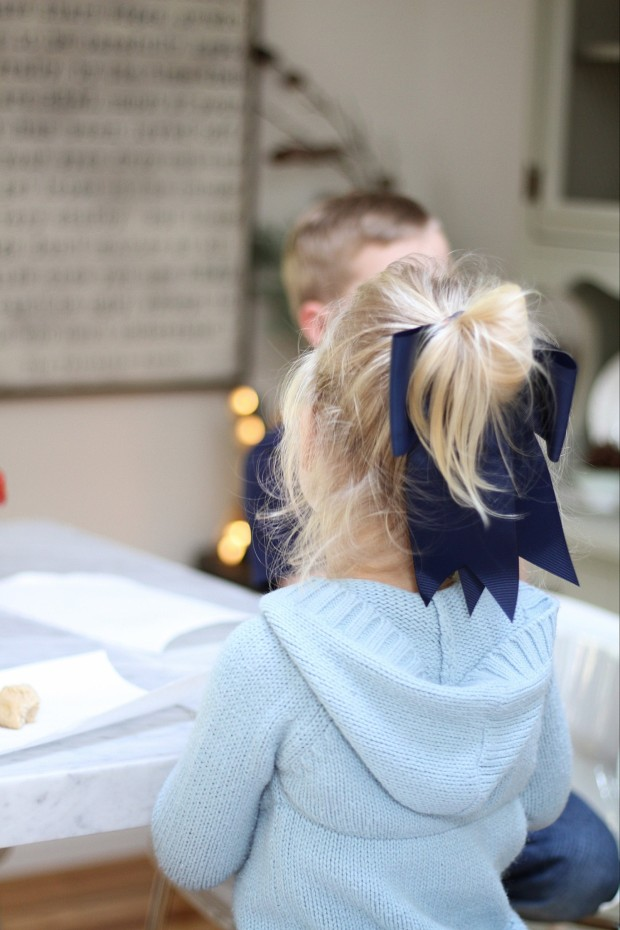 A little blonde girl at the table with a pony tail in her hair.