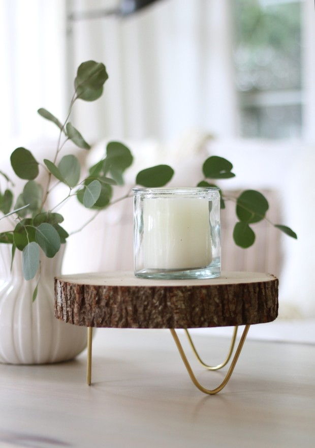 A round wood footed tray with a candle on it.
