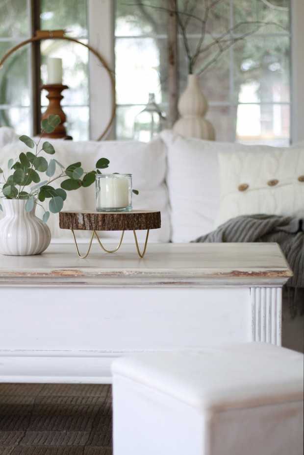 A round wooden tray in a white living room with eucapyptus plant in a vase beside it.