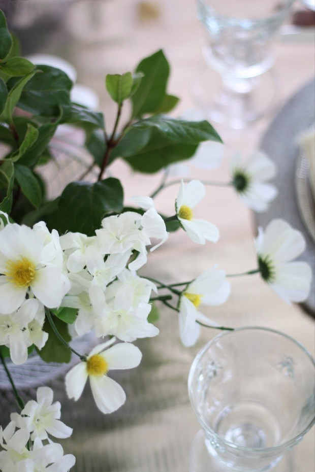 White flowers on the table beside a clear drinking glass.