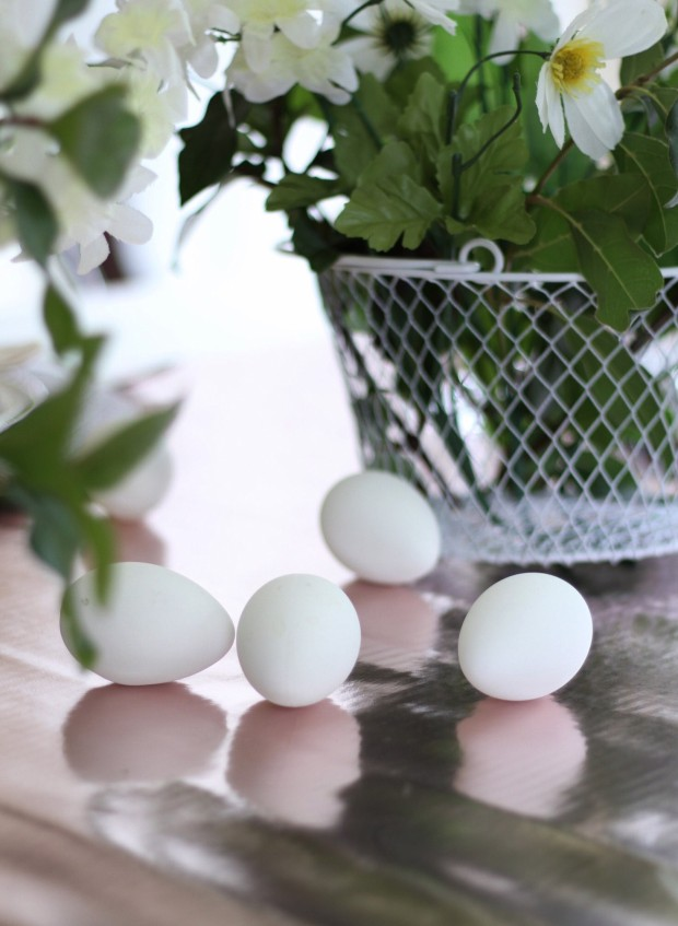Faux white eggs on the table beside the wire basket.
