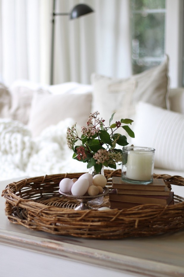 A wicker tray on a coffee table with the Easter eggs, a candle and a small vase with flowers on it to.