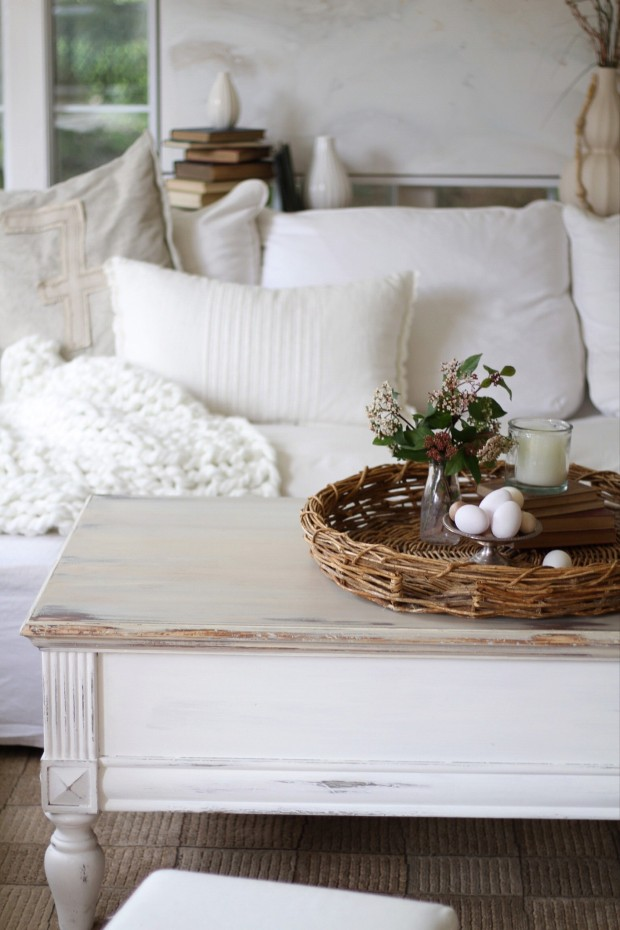A soft white living room with a distressed white coffee table in the middle of the room.