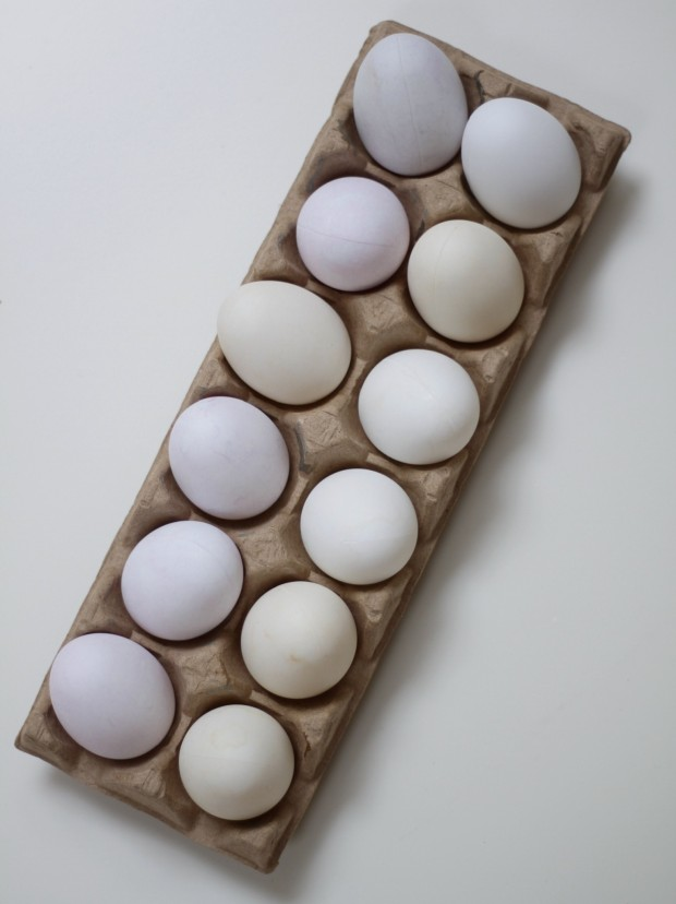 A dozen tea dyed Easter eggs in a carton.