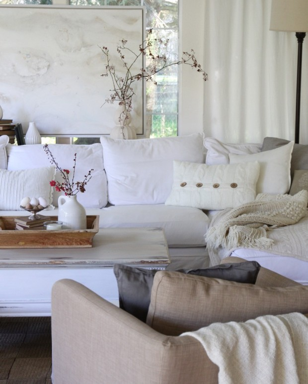 A neutral living room with a white sofa and white pillows.