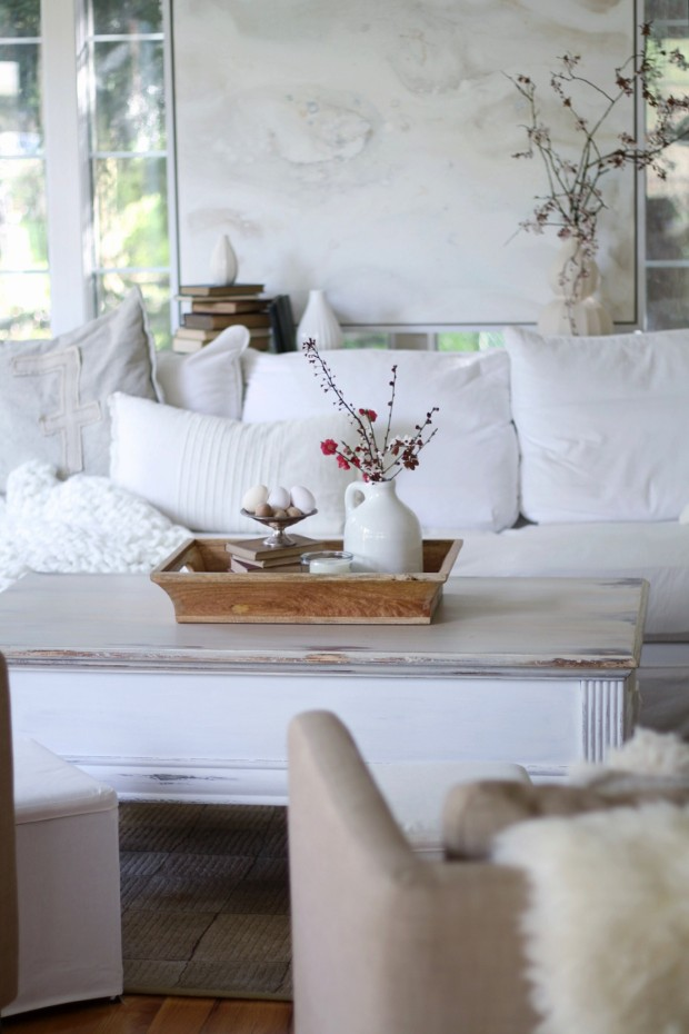 Whitewashed coffee table with a white vase on the table.