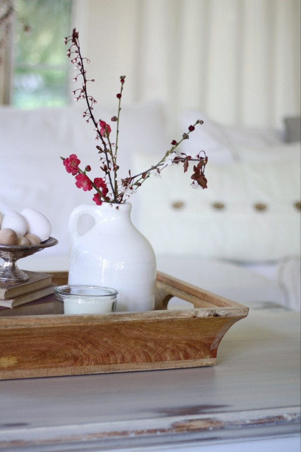 A wooden tray on the coffee table with a white vase on the tray.