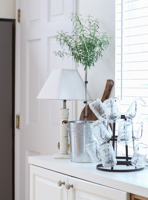 A white counter with a white lamp, glasses and a plant in a silver container.