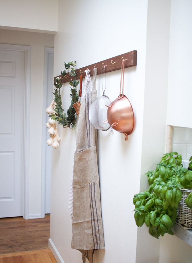 Laurel wreath, an apron, pots on hooks in the kitchen.