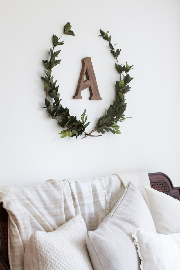 Two sprigs of laurel in a U shape with the letter A on the wall.