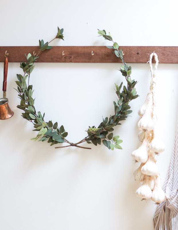 A DIY laurel wreath hanging on a coat rail.