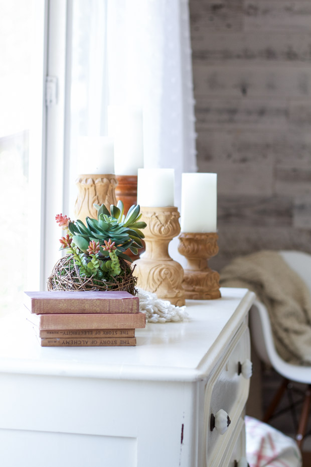 A white dresser with white candles and a grapevine planter on it beside books.