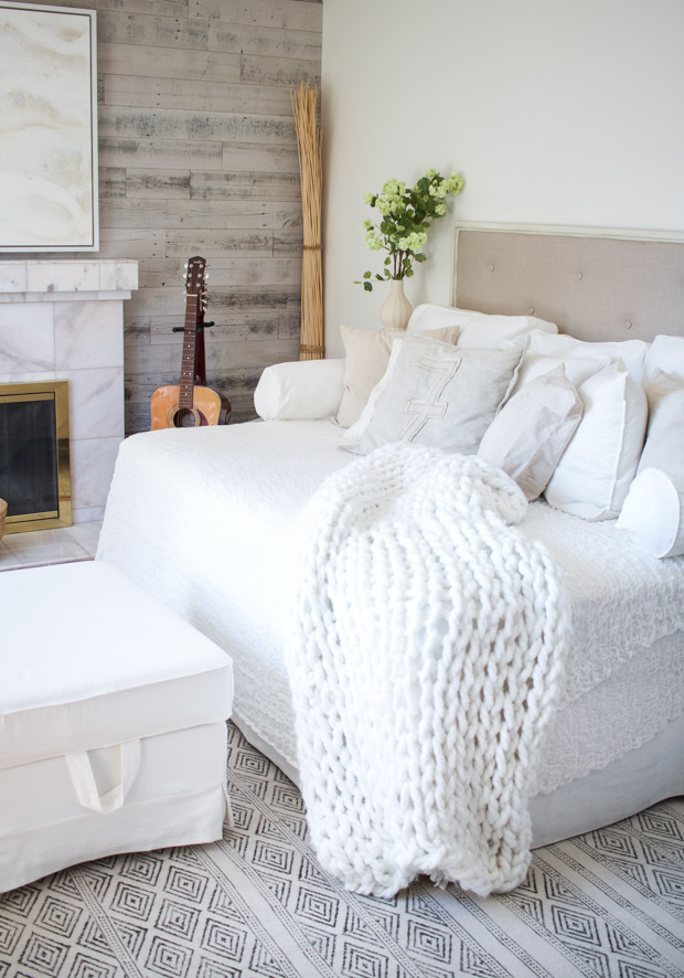 Soft white bed with tufted headboard and white ottoman.