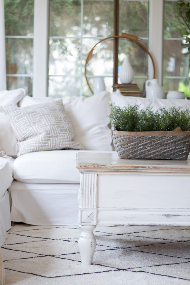 White couch with white wooden table and greenery in a basket on it.