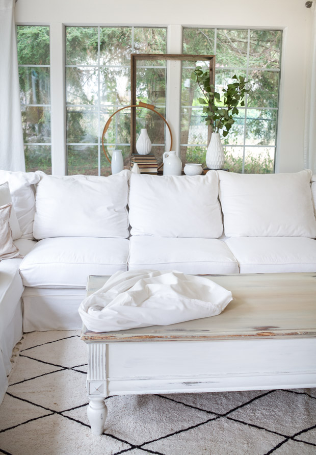 Fitting the white sheets together on the couch.