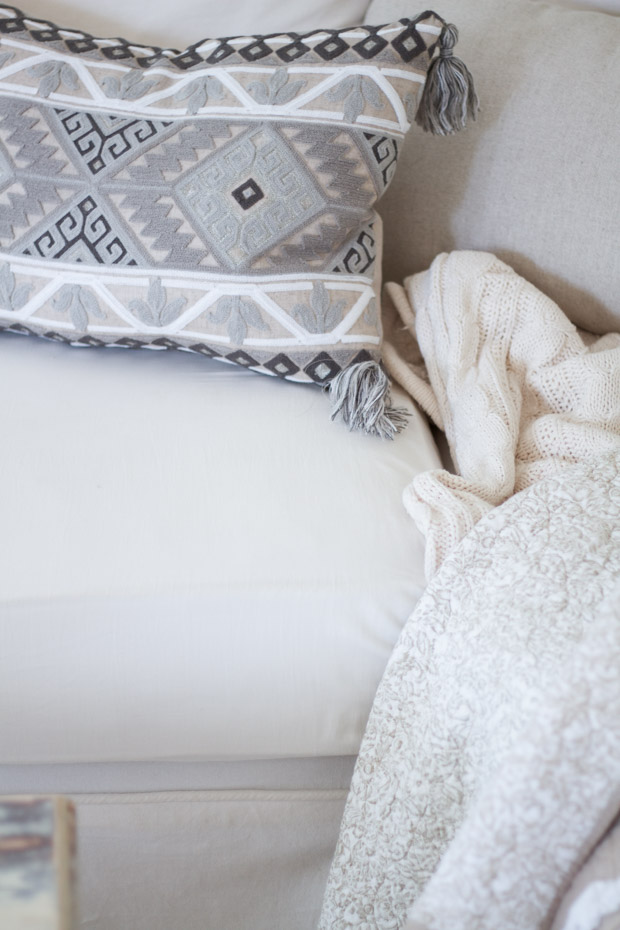 Pillow and blanket on white couch.