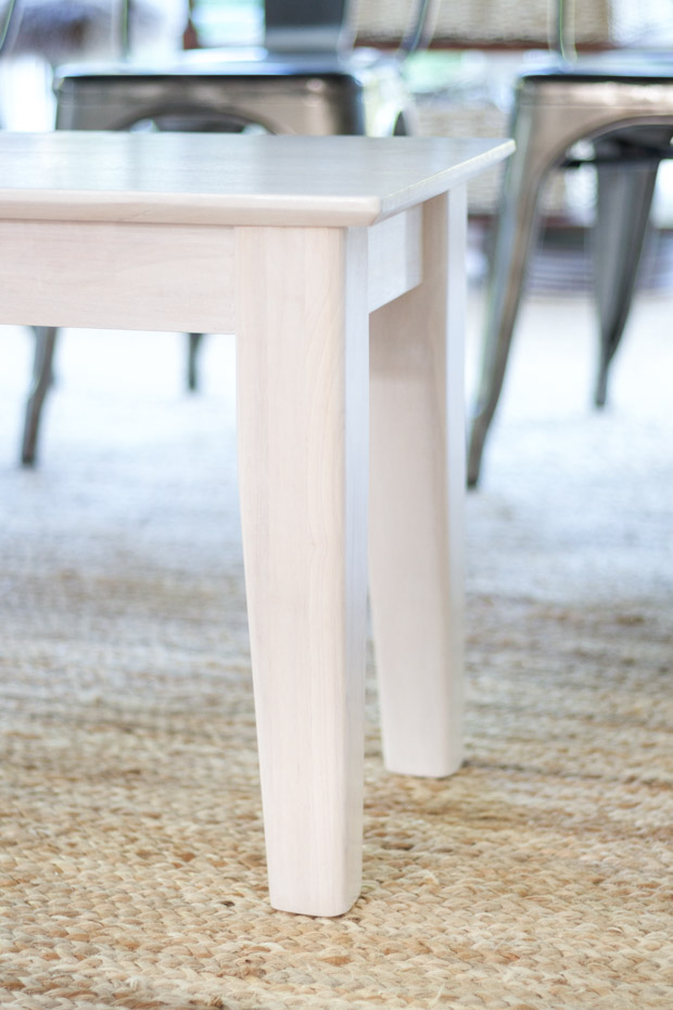 The white stained wood table in dining room.