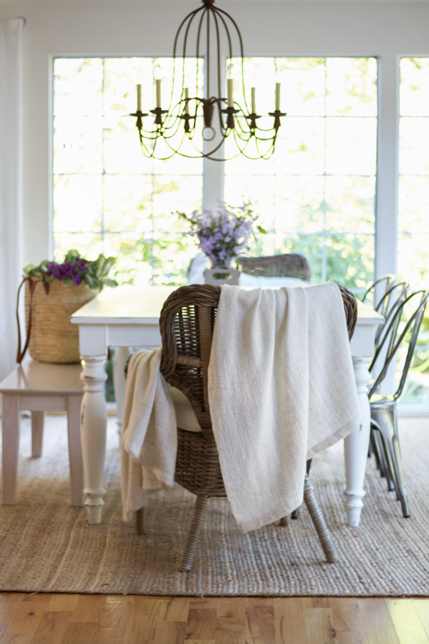 Bench with tote bag and chair with throw blanket in dining room.