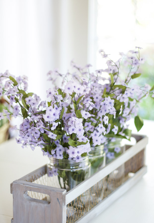 Pretty purple flowers in jars on table.