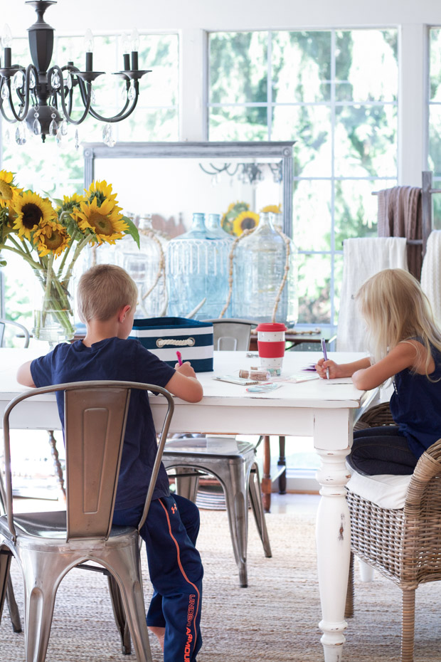 Children sitting at dining room table doing school work.