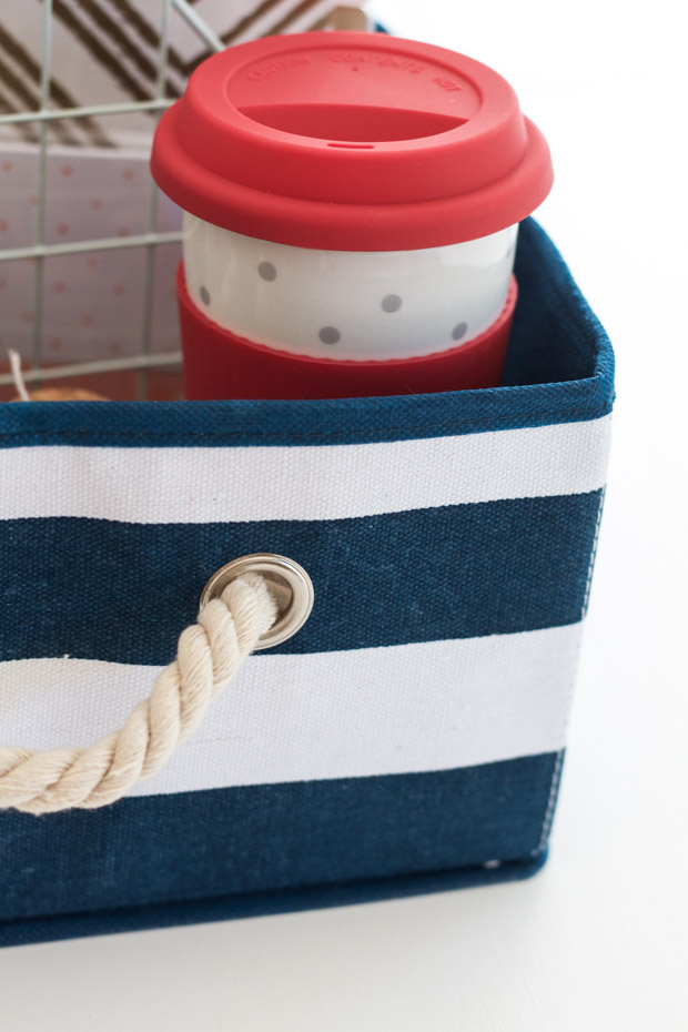 The red and white cup in the striped blue and white basket.