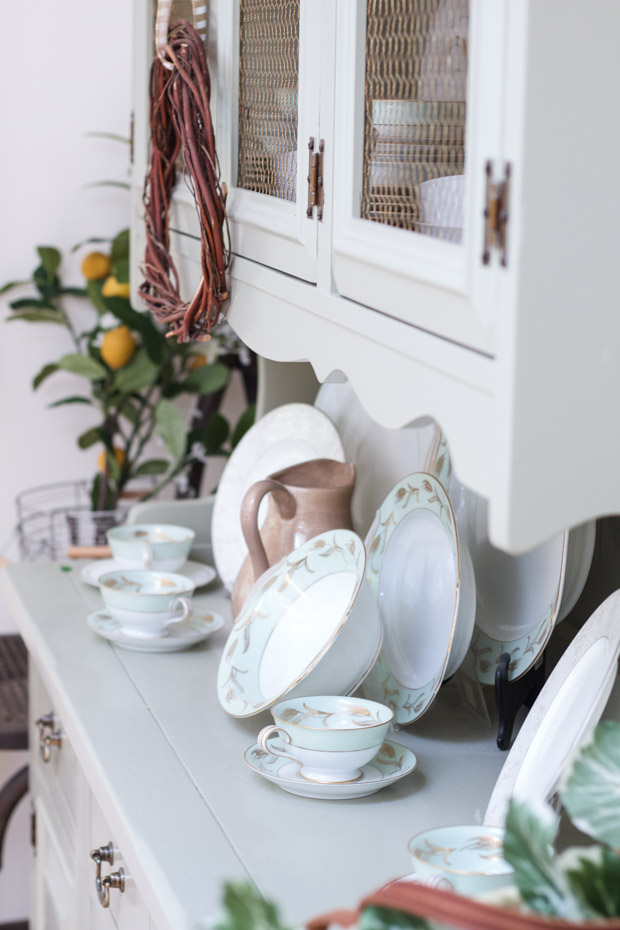 White dining room hutch with antique bowls and tea cups on top.