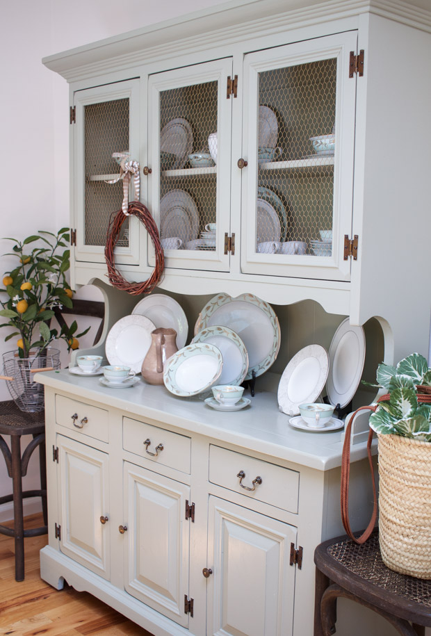 Antique bowls and cups mixed with new plates on white hutch in dining room.