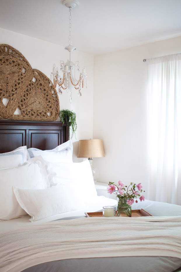 Large bed with white linens and a tray with a vase and pink flowers on it.