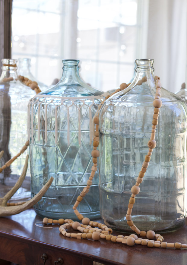 Two large glass jars with wooden beads around them.
