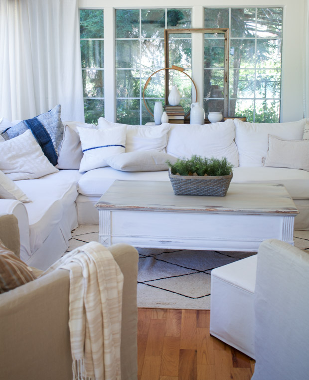 White couch in living room with distressed painted coffee table.