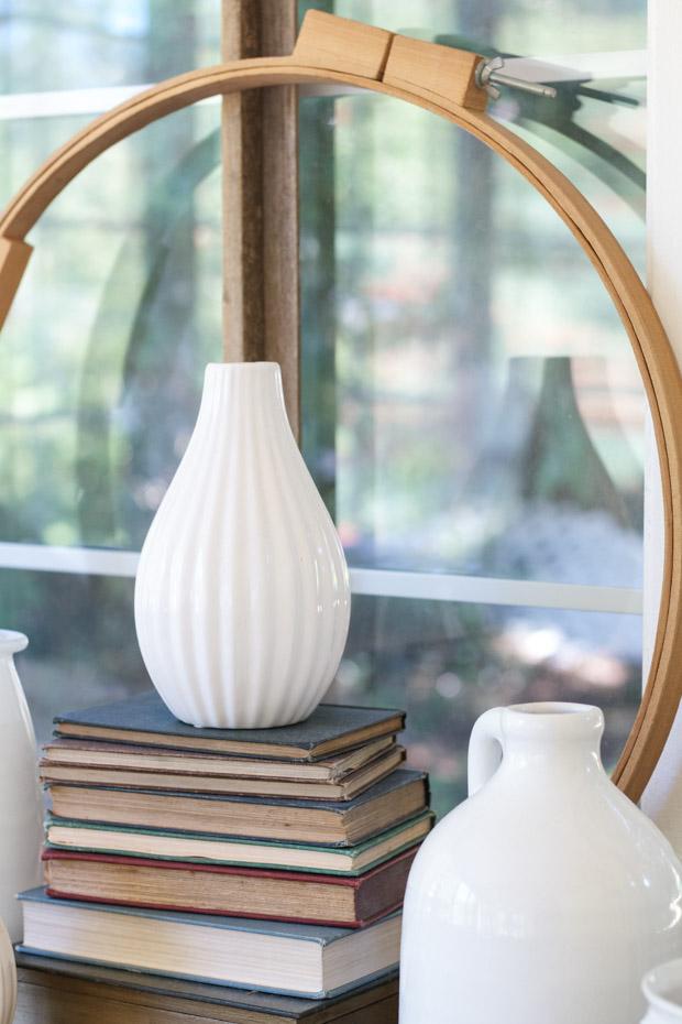 White thrift store vases on top of books on desk.