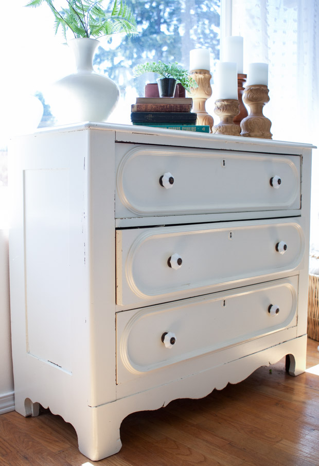 Vintage white dresser with candles on it.