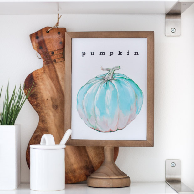The royal blue pumpkin printable in a wooden frame with a cutting board behind it on the shelf.