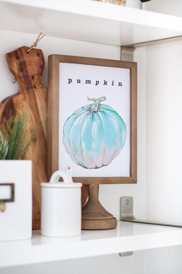 Blue pumpkin printable framed displayed on a ledge.