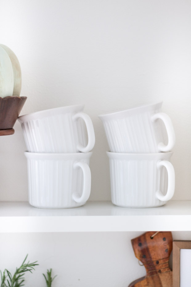 White coffee cups on the open shelf.