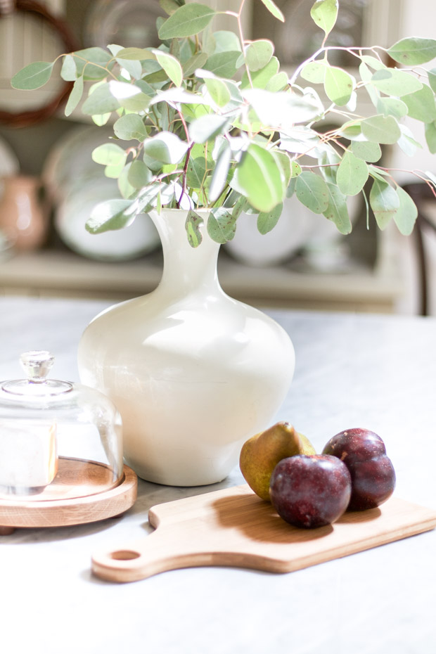 Eucalyptus in a white vase with plums and a pear on a wooden cutting board beside it.