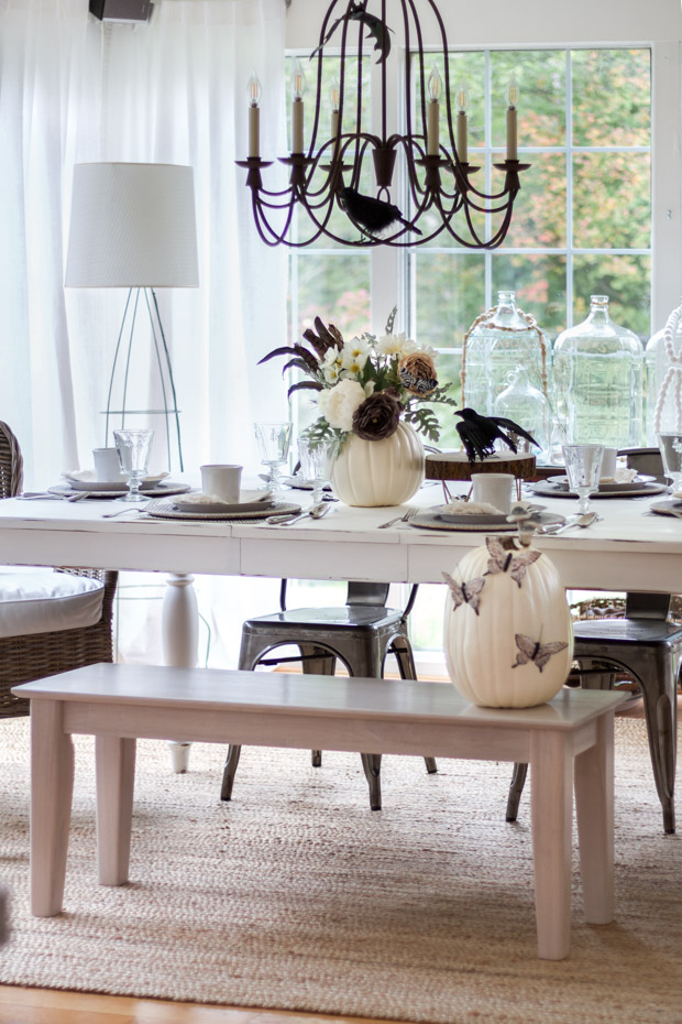 Dining room with white pumpkins, and butterflies and black crow on the table.
